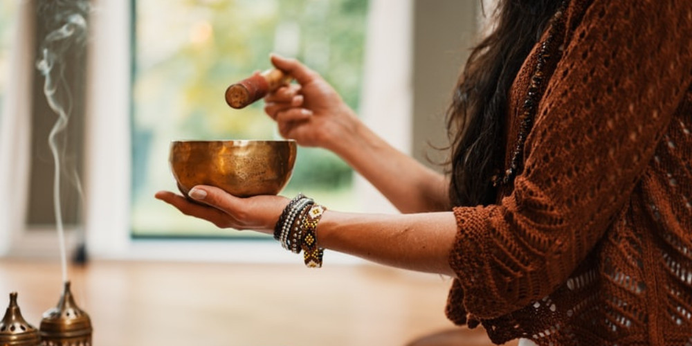 Woman playing the singing bowl  healing frequencies and Solfeggio Frequencies 417 hz 528 hz