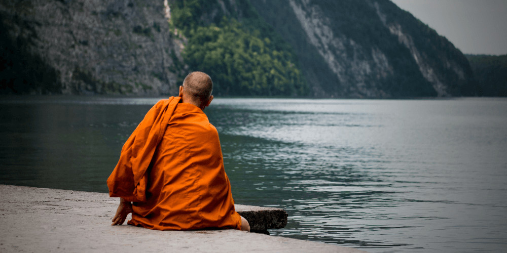 Monk sitting infront of a lake the vow of silence